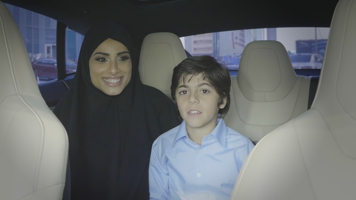 Muslim woman with a kid in a driverless car