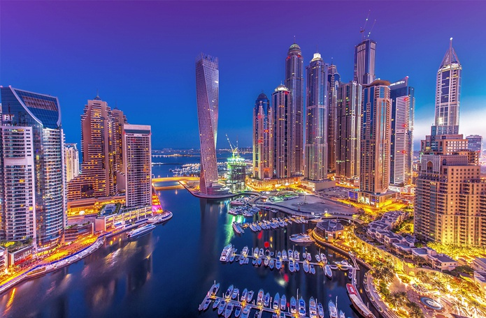 Dubai Marina lit up at night with Cayan Tower in the spotlight